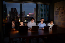 Three Businessman And Two Businesswoman Working With Computer Overtime At Night