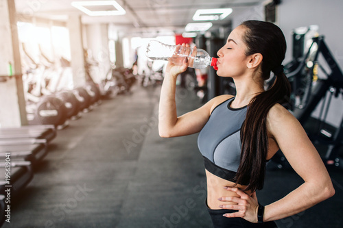Spoed Foto op Canvas Fitness Close up of a beautiful girl drinking water from the bottle. He is having some rest after workout. Cut view.