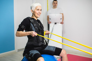 Beautiful senior woman doing exercises in electrical muscular stimulation suit with her personal trainer at rehabilitation center.