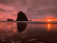 Haystack Rock Silhouette Reflects In The Water At Cannon Beach, Oregon. Flaming Red Afterglow As Sun Sets On The Horizon, Long Exposure Shot With Clouds In Motion Over Pacific Ocean.