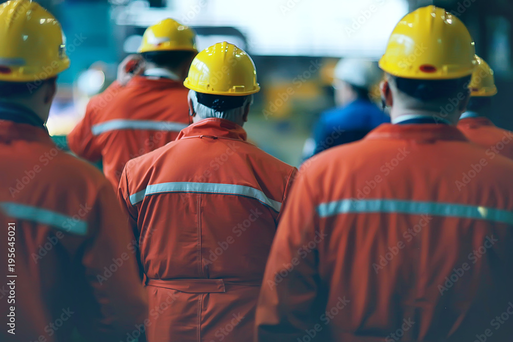 Fototapety, obrazy: workers  helmets at the factory, view from the back, group of workers,  change of workers in the factory, people go in helmets and uniforms for an industrial enterprise
