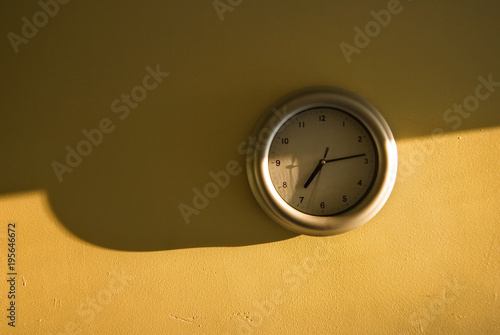 Photo  Analogue clock on the yellow wall showing 7:14 time, light from the side, long shadows emphasising early morning sun