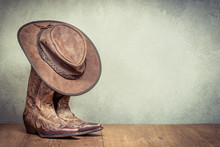 Wild West Retro Leather Cowboy Hat And Old Boots Front Concrete Wall Background. Vintage Instagram Style Filtered Photo
