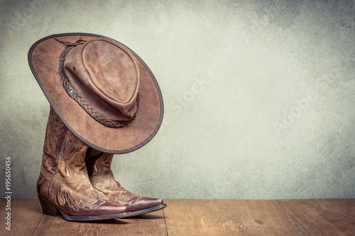 Fényképezés Wild West retro leather cowboy hat and old boots front concrete wall background