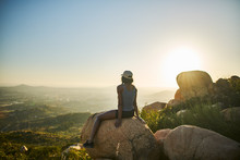 Fit Hiker At Top Of Mountain Sitting On Huge Rock Watching Sun Set With San Diego In The Distance