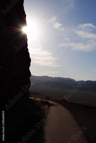 A cliff walkway, with the sun behind a cliff, overlooking Lake Mead Poster