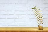 Fototapeta Kamienie - Złoty liść na półce na tle białej ścianie z cegły.
