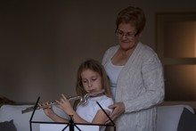 Girl Playing Flute With Her Grandmother In Living Room