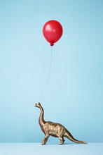 Toy Dinosaur And Balloon Against Blue Background