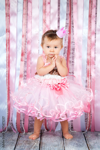 2db6a84fcf16 A sweet little girl in a crown and a beautiful pink dress is raising ...