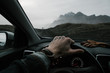 Anonymous man travelling and holding tattooed hands on the wheel while driving a car on icelandic mountains background