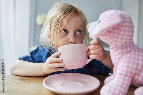 Child drinking her milk from a cup and saucer