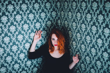 Porrait Of A Ginger Woman Leaning On A Damask Wallpaper Decorated Wall