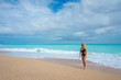 beautiful blonde girl in a black bathing suit on an empty Caribbean beach