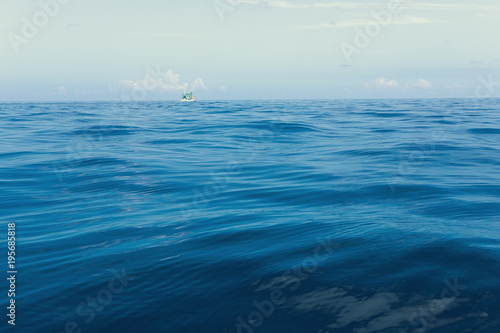 Poster Zee / Oceaan minimal photography of fishery boat floating over blue sea wave