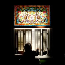 A Small Boy Opens The Shutters To Peek Out A Window.