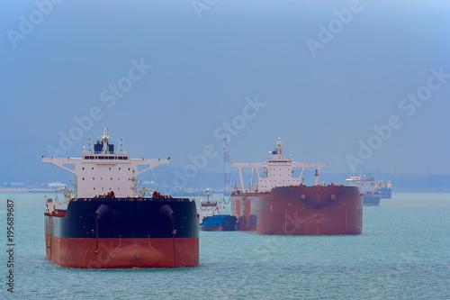 Loading anchored oil supertanker via a ship-to-ship oil transfer