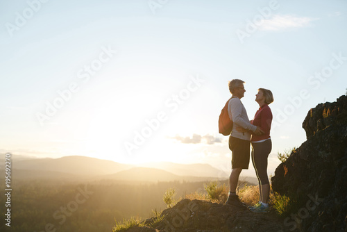 City on the water Fit, active middle age couple hiking together at sunset