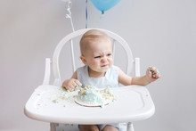 Baby Making Funny Face While Eating First Birthday Cake