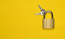 Golden Closed Lock With Keys On A Yellow Background. Copy Space. Top View.