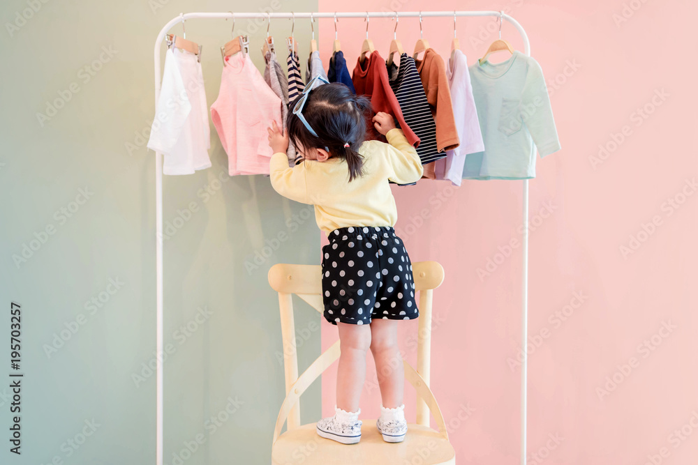 Fototapety, obrazy: Soft Focus of a Two Years Old Child Choosing her own Dresses from Kids Cloth Rack