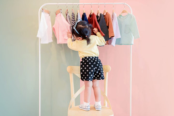 Fototapeta Soft Focus of a Two Years Old Child Choosing her own Dresses from Kids Cloth Rack