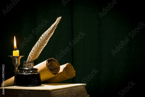 Photo The concept of education and writing, a pen in an inkwell and a candle with a ca