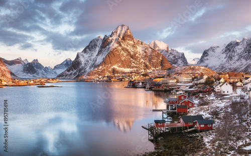 Photo Stands Arctic Houses in the Lofoten islands bay. Natural landscape during sunrise