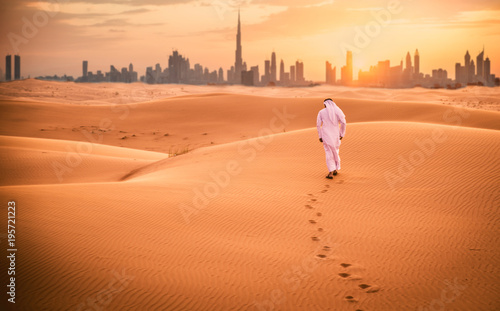 obraz dibond Arabic man with traditional emirates clothes walking in the desert