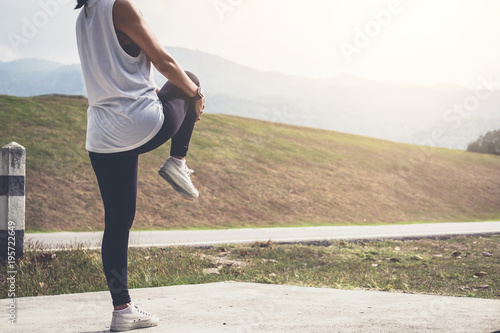 Fototapeta Athlete woman doing some stretching exercises legs before running on outdoor obraz