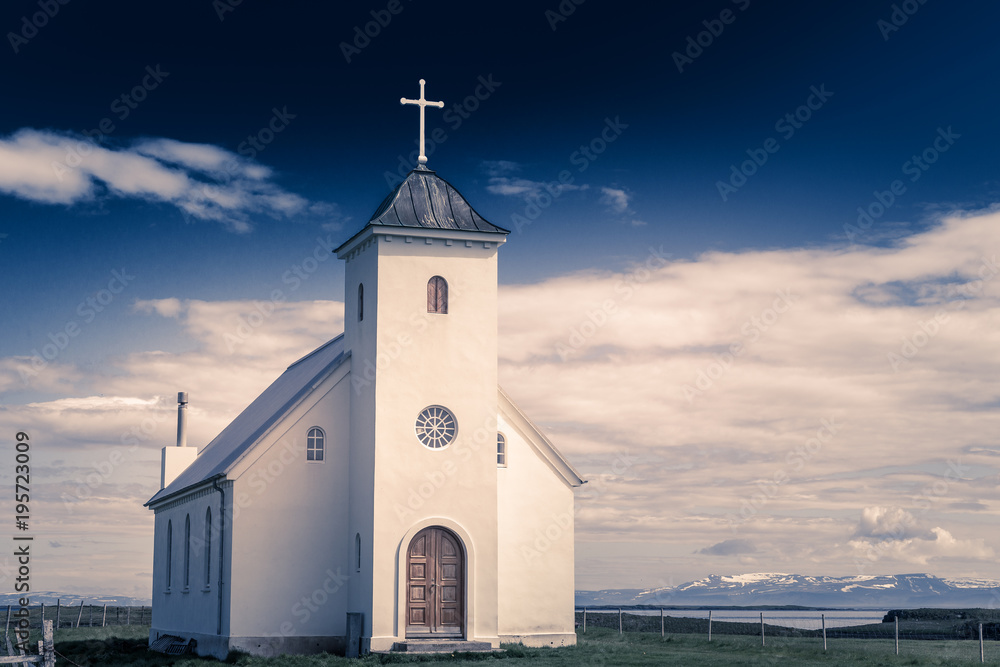 Fototapety, obrazy: Flateyjarkirkja white lutheran church with meadow in foreground and sea  fjord with dark blue sky and mountains in the background, Flatey, Iceland