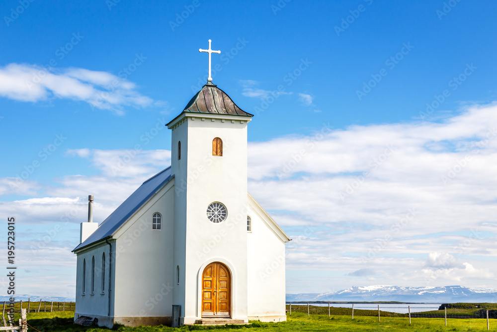 Fototapeta Flateyjarkirkja white lutheran church with meadow in foreground and sea  fjord with blue sky and mountains in the background, Flatey, Iceland