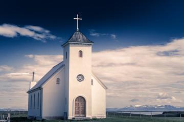 Flateyjarkirkja biały kościół lutniczy z łąką na pierwszym planie i fiordem morskim z ciemnoniebieskim niebem i górami w tle, Flatey, Islandia