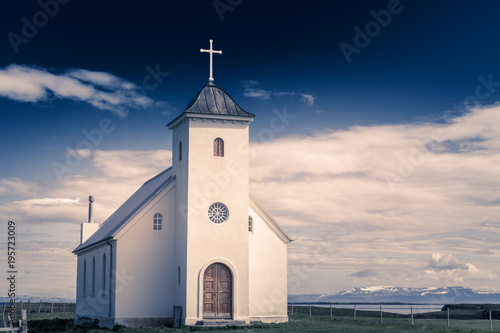 Edifice religieux Flateyjarkirkja white lutheran church with meadow in foreground and sea fjord with dark blue sky and mountains in the background, Flatey, Iceland