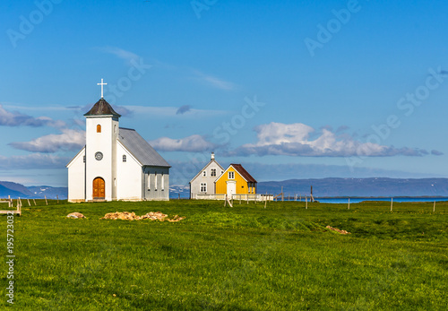 Edifice religieux Flateyjarkirkja white lutheran church and couple of living huts with meadow in foreground and sea fjord with blue sky in the background, Flatey, Iceland