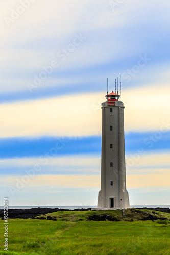 Foto op Aluminium Vuurtoren Malariff lighthouse tower standing on the seashore with striped sky in the background, Western Iceland