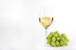 canvas print picture - Weiswein in einem Glas mit einer Traube im Glas und Weintrauben nebenliegend