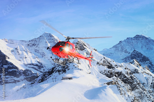 Red helicopter flying in winter Swiss Alps mountain under snow Mannlichen in winter