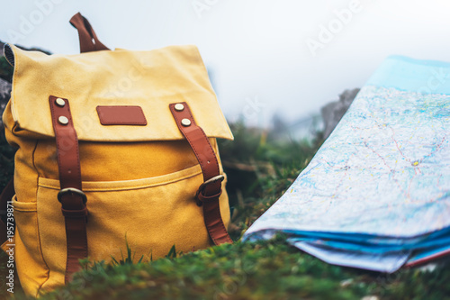 Obraz Hipster hiker tourist yellow backpack and navigation map europe on background green grass nature, blurred panoramic landscape, traveler holiday concept, view planning way road in trip vacation - fototapety do salonu