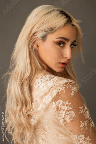Photo  Beautiful blonde woman portrait wearing lace dress and looking over shoulder