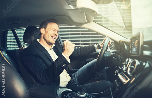 Fotografia  Businessman fist pumping while driving in his car in the city