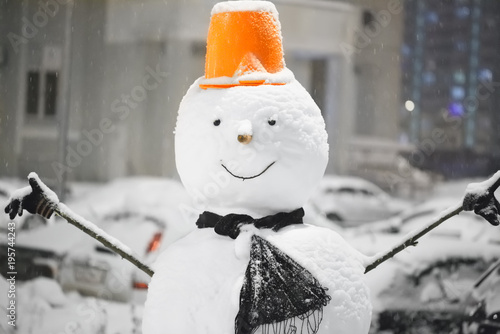 Snowman on a blurred background in gray with blue lights of the cityscape. Closeup of smiling snowman with orange hat, scarf and carrot nose, outdoors in snowfall. New year snow concept Happy holiday