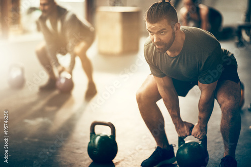 Poster Fitness Man lifting dumbbells during a workout class at the gym