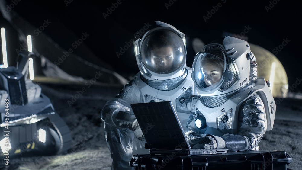 Fototapety, obrazy: Two Astronauts Wearing Space Suits Work on a Laptop, Exploring Newly Discovered Planet, Send Communicating Signal to Earth. Space Travel, Interstellar Exploration and Colonization Concept.