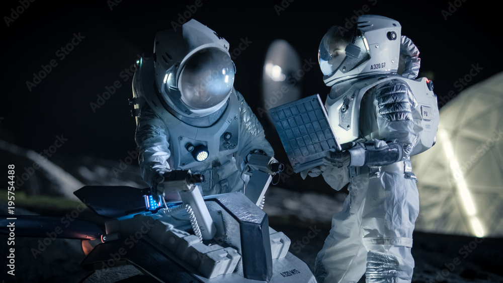 Fototapety, obrazy: Two Astronauts in Space Suits on an Alien Planet Prepare Space Rover for Planet's Surface Exploration Expedition, Use Laptop. Space Travel and Solar System Colonization Concept.