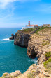 Blue sea and lighthouse on top of cliff at Cabo Sao Vicente, Algarve region, Portugal