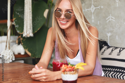 Deurstickers Kruidenierswinkel Photo of cheerful relaxed female model recreats at coffee shop, has positive smile, eats summer sweet tasty dessert, sits on comfortable sofa. People, eating, recreation and lifestyle concept