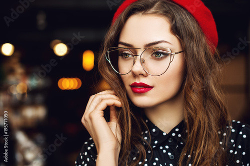 Close up portrait of young beautiful woman wearing stylish glasses, red beret, polka dot blouse. Model looking aside. Lights on background. Copy, empty space for text