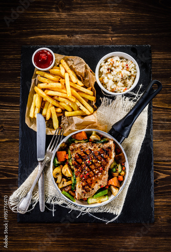 In de dag Grill / Barbecue Grilled steak with french fries and vegetables served on black stone on wooden table