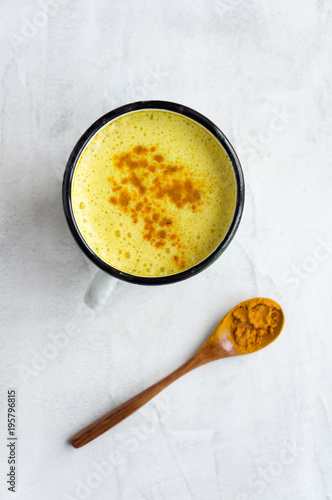 Turmeric latte, Golden milk. Hot healthy drink. Concrete background. Vertical photo. Top view.
